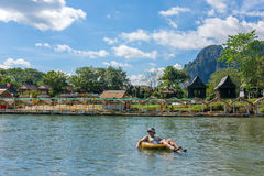 Unidentified tourist enjoy tubing in Song River in Vang Viang village, Laos. Vang Vieng, Laos - January 19, 2017: Unidentified tourist enjoy tubing in Song Stock Images