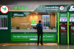 Unidentified tourist exchanges money in Bangkok airport, Thailan Royalty Free Stock Image