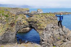 Unidentified tourist standing at Gatklettur Stone Arch,Iceland Stock Photos