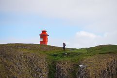 Unidentified tourist walking up to the cliff in Stykkisholmur,Ic Stock Image