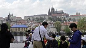 Unidentified tourists on Charles Bridge (Karluv Most) in afternoon, a famous historic bridge in Prague. PRAGUE, CZECH REPUBLIC -SUMMER 2015: Unidentified stock footage