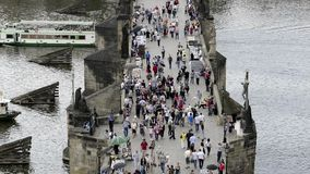 Unidentified tourists on Charles Bridge (Karluv Most) in afternoon, a famous historic bridge in Prague. PRAGUE, CZECH REPUBLIC -SUMMER 2015: Unidentified stock video footage