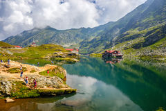 Unidentified tourists enjoy the sights of Balea Lake at 2,034 m altitude in Fagaras Mountains Stock Photo