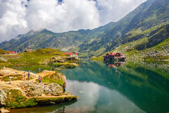 Unidentified tourists enjoy the sights of Balea Lake at 2,034 m altitude in Fagaras Mountains Royalty Free Stock Image