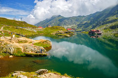 Unidentified tourists enjoy the sights of Balea Lake at 2,034 m altitude in Fagaras Mountains Royalty Free Stock Photo