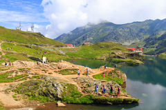 Unidentified tourists enjoy the sights of Balea Lake at 2,034 m altitude on July 21 Stock Images