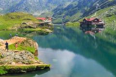 Unidentified tourists enjoy the sights of Balea Lake Stock Images