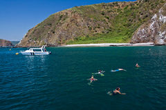 Unidentified tourists enjoying a daytrip. MANABI, ECUADOR - JUNE 4, 2012: Unidentified tourists enjoying a daytrip snorkeling in beautiful paradise beach in Stock Photo