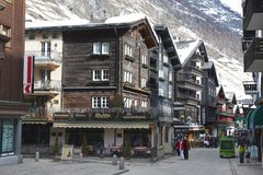 Unidentified tourists explore traditional wooden houses street in Zermatt, Switzerland. Royalty Free Stock Image