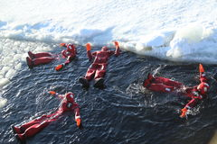 Unidentified tourists geared up with a survival suit ice swim in frozen Baltic Sea. Stock Photos