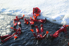 Unidentified tourists geared up with a survival suit ice swim in frozen Baltic Sea. Royalty Free Stock Photography