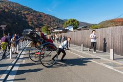 Unidentified tourists on Japanese traditional rickshaw for sightseeing around Arashiyama in Kyoto. KYOTO,JAPAN-NOV26:Unidentified tourists on Japanese Royalty Free Stock Photo
