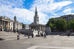 Unidentified  tourists near The church of St Martin's-in-the-Field  and  National Gallery  on Trafalgar Square.  London Stock Images