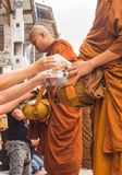 Unidentified tourists offering sticky rice to Buddhist monk in Royalty Free Stock Photos