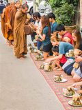 Unidentified tourists offering sticky rice to Buddhist monk in Royalty Free Stock Image