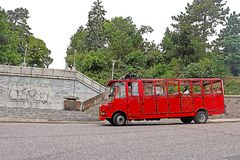 Unidentified tourists in red vintage bus on the streets of Bratislava city near Slavin memorial monument