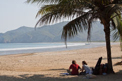 Unidentified tourists relaxing under a palm tree Royalty Free Stock Photography