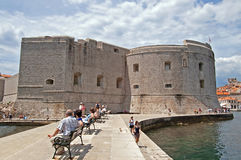 Unidentified tourists are resting on the embankment, Dubrovnik Royalty Free Stock Images