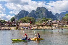 Unidentified tourists are rowing kayak boats in Nam Song River in Vang Vieng, Laos. Vang Vieng, Laos - January 19, 2017: Unidentified tourists are rowing kayak Royalty Free Stock Photography