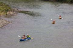 Unidentified tourists are rowing kayak boats in Song River. Stock Images