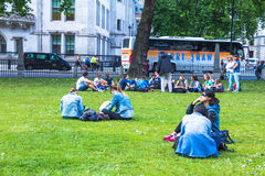 Unidentified tourists  tourists resting on the grass near Westminster Abbey Royalty Free Stock Images