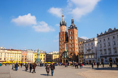 Unidentified tourists visiting main market square in front of St. Mary's Basilica, in Krakow Stock Image