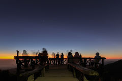 Unidentified tourists  are waiting for sunrise at old wooden view Stock Photo
