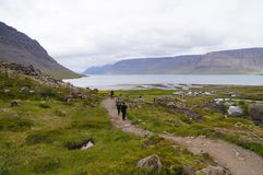 Unidentified tourists walking to Dynjandi Waterfall,Iceland. Stock Image