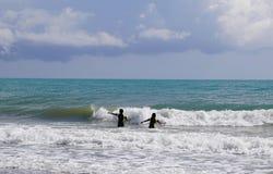 Unidentified two children enjoying wavy Mediterranean royalty free stock photos