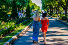 Unidentified unrecognizable young blonde and brunette women walk Stock Photo