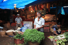 Unidentified vegetable seller looks for customers in the crowded market Royalty Free Stock Images