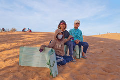 Unidentified Vietnamese young boys with Sandboards for tourists on Red Sand dunes. Mui Ne. Vietnam Stock Image