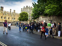 Unidentified visitors queuing in front of the  Windsor Castle. UK. Unidentified visitors queuing in front of the  medieval Windsor Castle. Windsor Castle is a Royalty Free Stock Photos