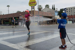 Unidentified volunteer boy throwing water in a runner Stock Image