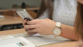 Unknown young woman holding smartphone. Unidentified woman with beautiful manicure in white lace shirt and with accessories on hands sit at wooden desk with stock video