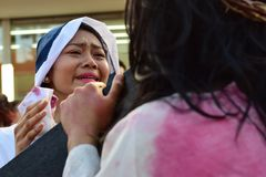 Unidentified woman crying in pity approach role playing Jesus Christ. San Pablo City, Laguna, Philippines - April 14, 2017: Unidentified woman crying in pity Stock Photography