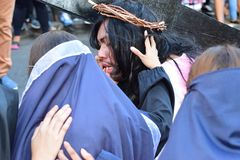 Unidentified woman crying in pity approach role playing Jesus Christ. San Pablo City, Laguna, Philippines - April 14, 2017: Unidentified woman crying in pity Stock Photos