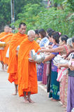 An unidentified woman Gives food to a monk Royalty Free Stock Photos