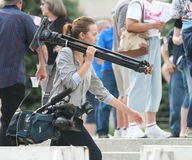 Unidentified woman reporter carrying camera equipment Stock Photos