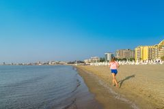 An unidentified woman running in the morning on a beautiful beach in Sunny Beach on the Black Sea coast of Bulgaria. Blue bulgarian coastline copy space stock images