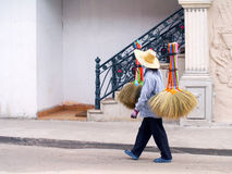 Unidentified woman sells brooms on a street. Royalty Free Stock Images
