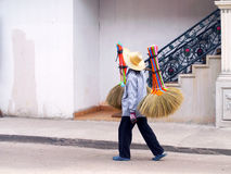 Unidentified woman sells brooms on a street. Stock Images