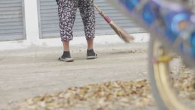Unidentified woman sweeping the leaves with broom in the park.