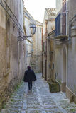 Unidentified woman walking away in ancient, typical narrow and cobblestone street in Erice, Sicily, Italy Royalty Free Stock Photo