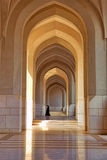 Unidentified woman walking under arch of sultan's building complex, in Muscat stock photos