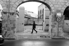 The unidentified woman walks between the arch of aqueduct, Wignacourt Aqueduct, Malta. Malta - 14 Jan 2016: The unidentified woman walks between the arch of Stock Image
