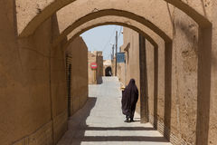 An unidentified woman walks down the narrow streets of Yazd Royalty Free Stock Photo