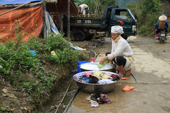 Unidentified woman washing clothes in a village of rural district of Quan Ba Stock Image
