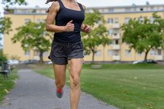 Unidentified woman wearing tank top and shorts. Unidentified woman wearing black tank top and shorts jogging along sidewalk in open park and building in royalty free stock photo