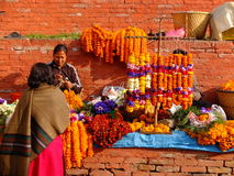 Unidentified women are making worship flowers in Bhaktapur Durbar Square area, Kathmandu, Nepal. Royalty Free Stock Image
